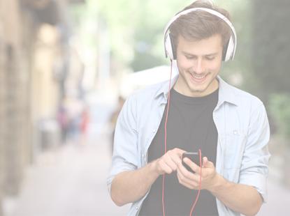 Mladý muž se sluchátky přes hlavu poslouchá hudbu z mobilu